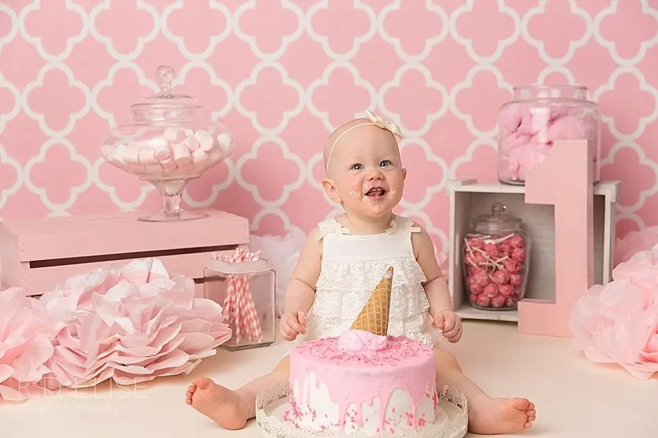 Baby girl in white dress in front of pink backdrop eating cake during candy themed cake smash.