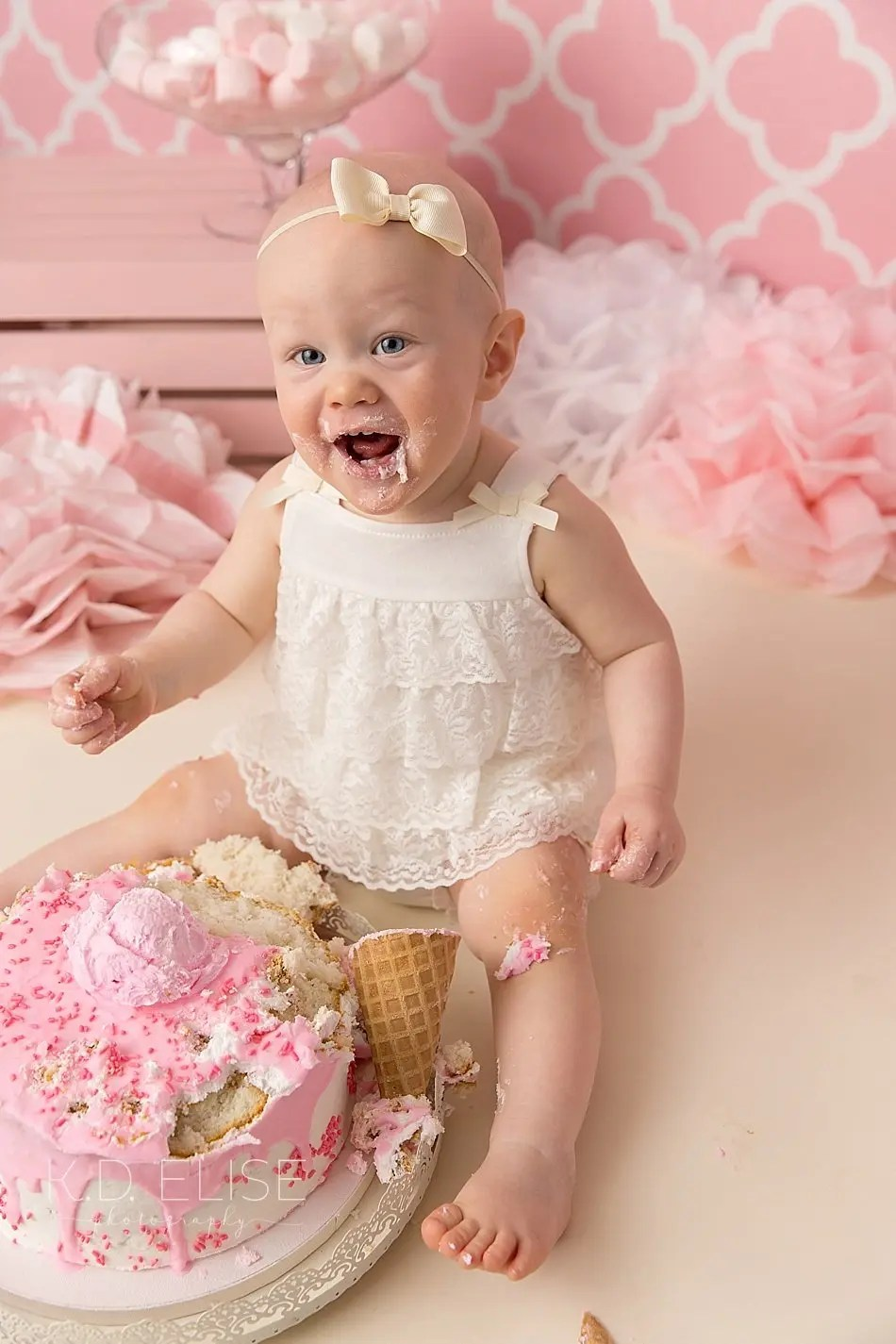 Baby girl smiles while eating cake during candy themed cake smash with Colorado Springs photographer K.D. Elise Photography.