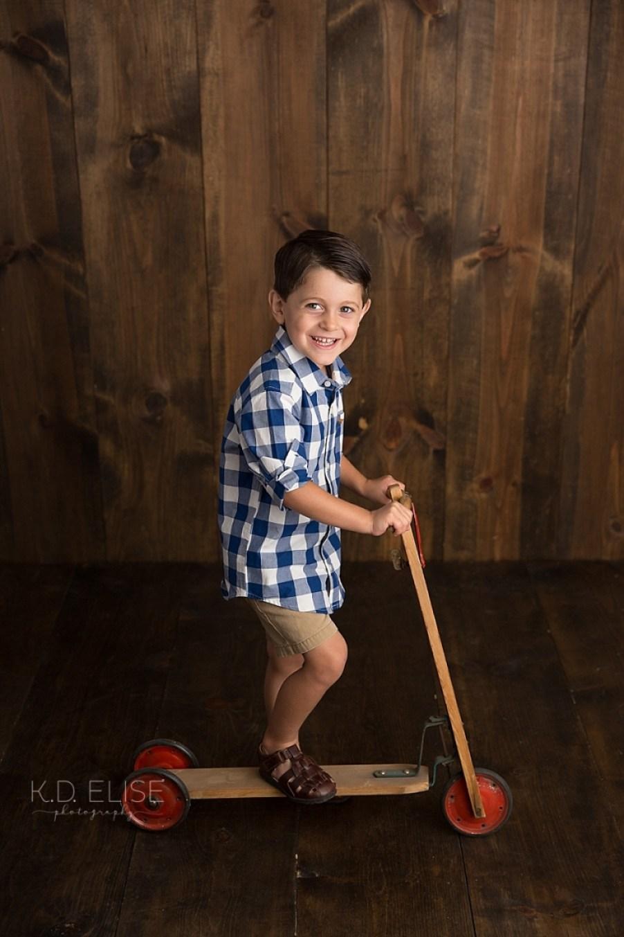 Little boy on a vintage scooter.