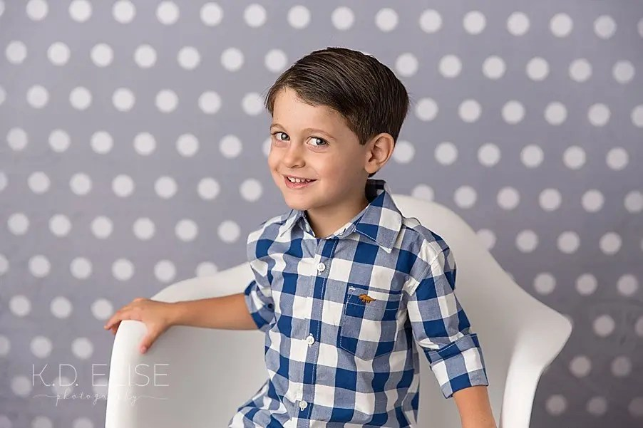 Little boy in a blue and white checked shirt sitting in a white chair in front of a polka dot backdrop.