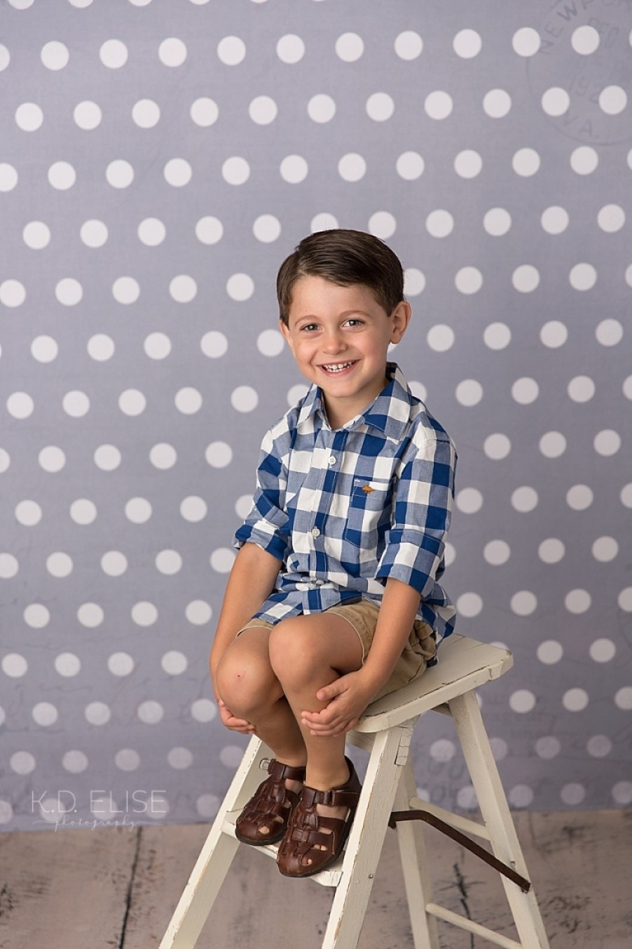 Four year old boy in a white and blue checked shirt sitting on a vintage white ladder.