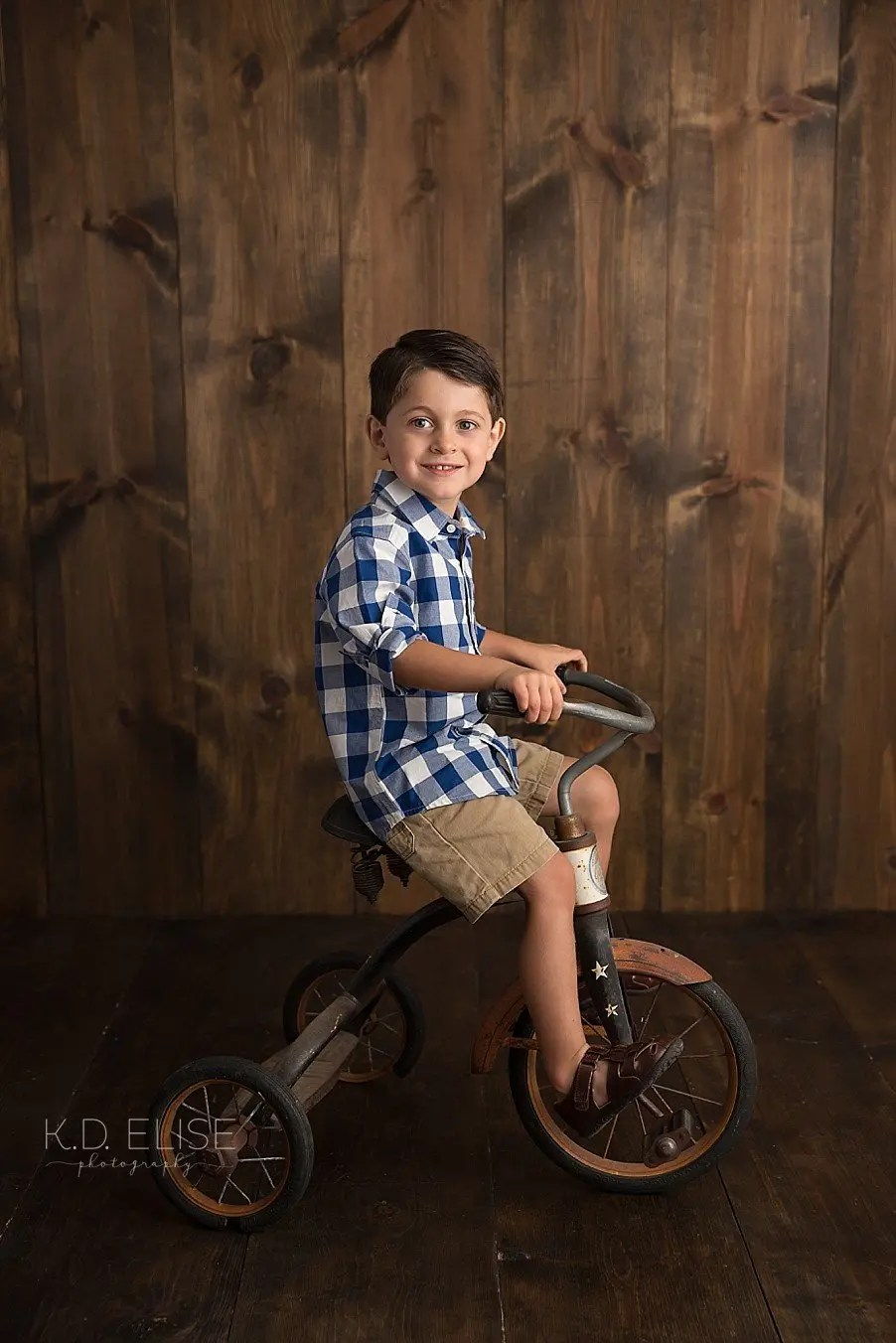 Four year old boy riding a vintage tricycle.