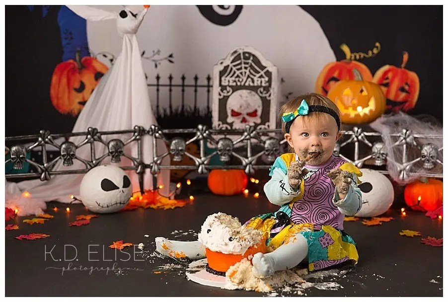 One year old baby girl eating cake in front of Nightmare Before Christmas themed set.