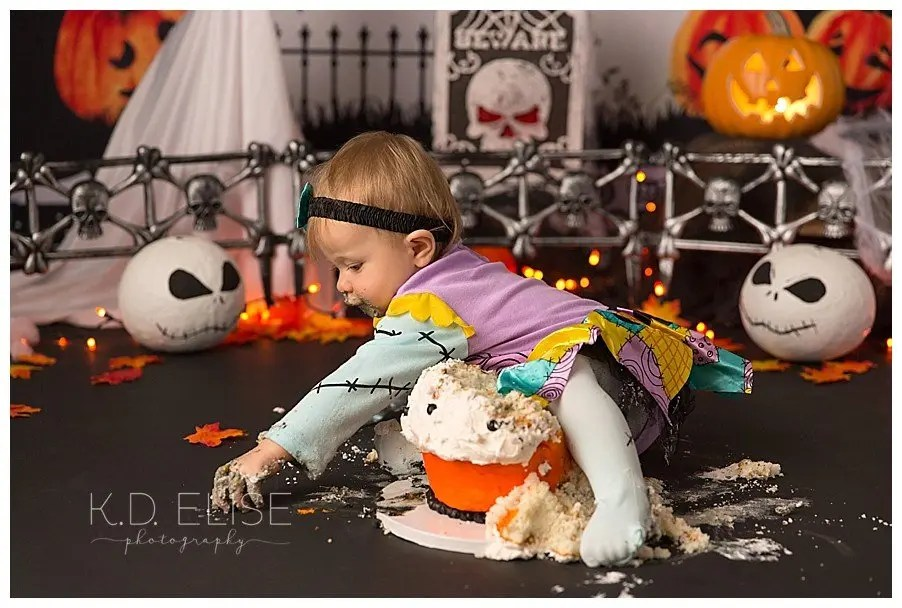 Baby girl crawling over her birthday cake during Nightmare Before Christmas themed cake smash by K.D. Elise Photography.