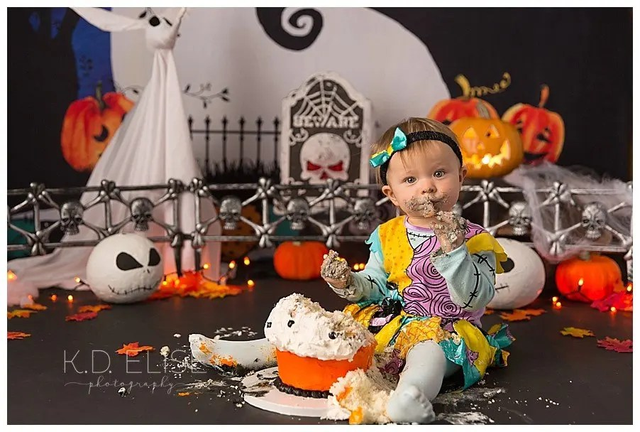 Baby girl covered in cake during Nightmare Before Christmas themed cake smash by Colorado cake smash photographer K.D. Elise Photography