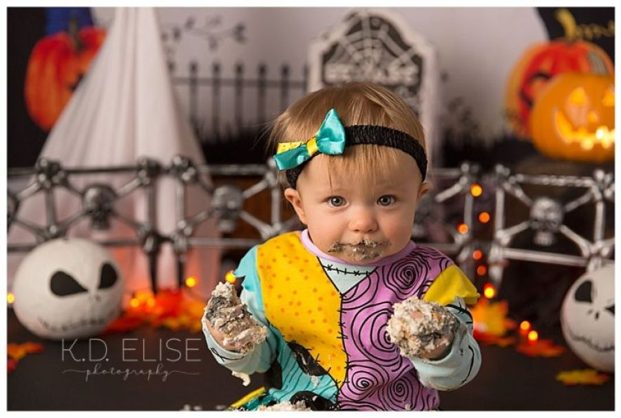 Close up photo of baby girl with cake on her hands and face during Nightmare Before Christmas themed cake smash.