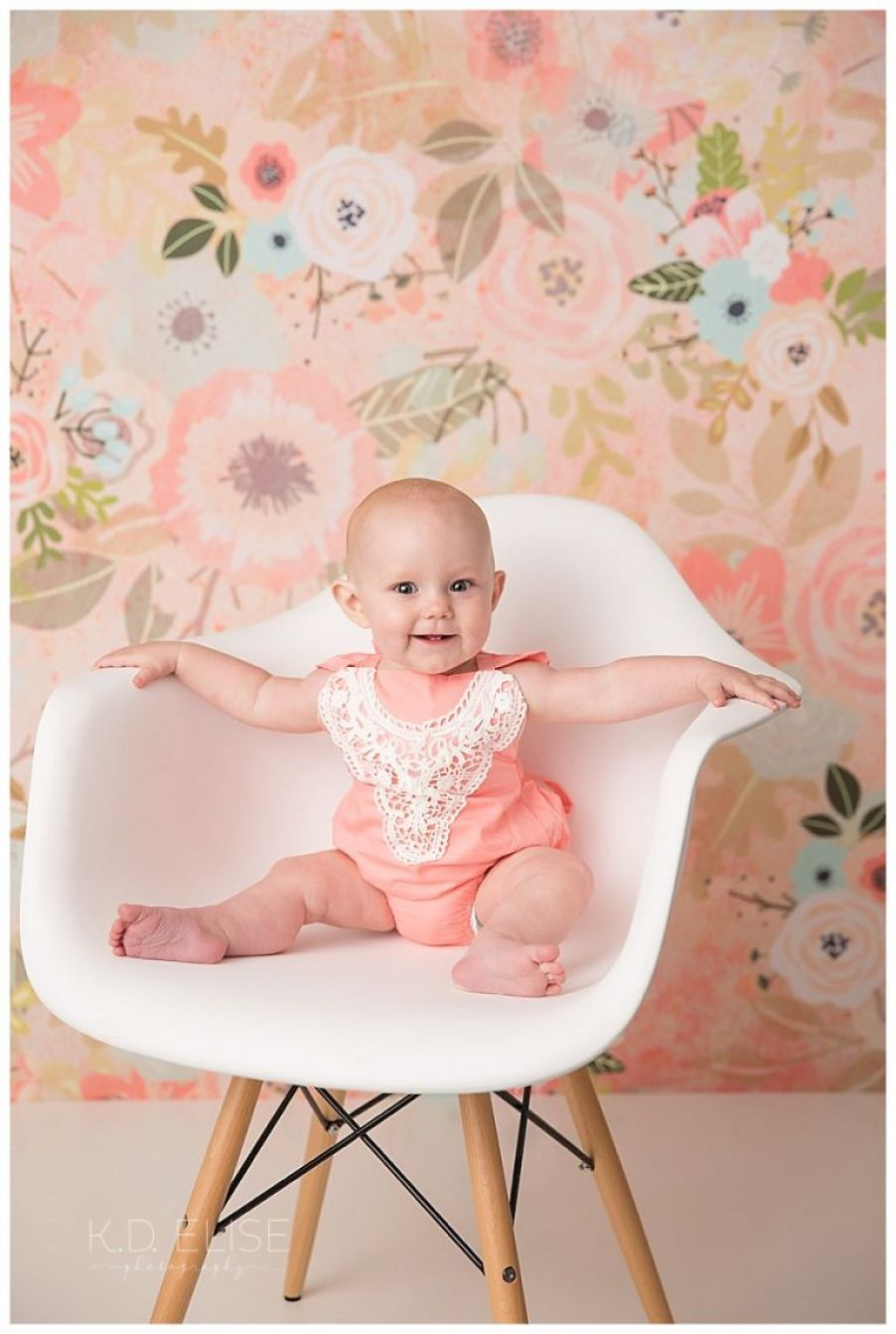 Baby girl in a white chair sitting in front of a floral backdrop.