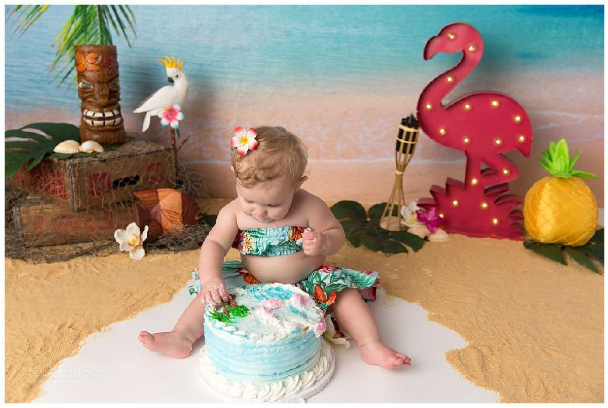 Baby girl eating cake during luau themed cake smash by Pueblo photographer K.D. Elise Photography.