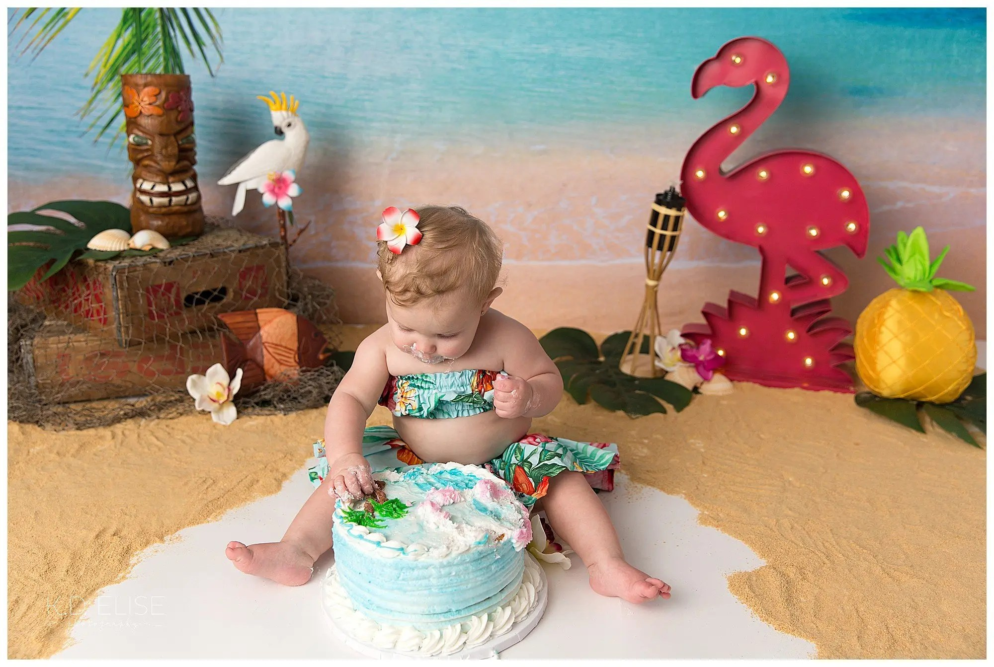 Baby girl eating cake during luau themed cake smash by Pueblo photographer K.D. Elise Photography.