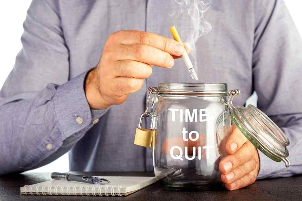 A man standing in front of a desk with a pen and paper, dropping a cigarette into a jar with the words 'Time to Quit' written on the side.