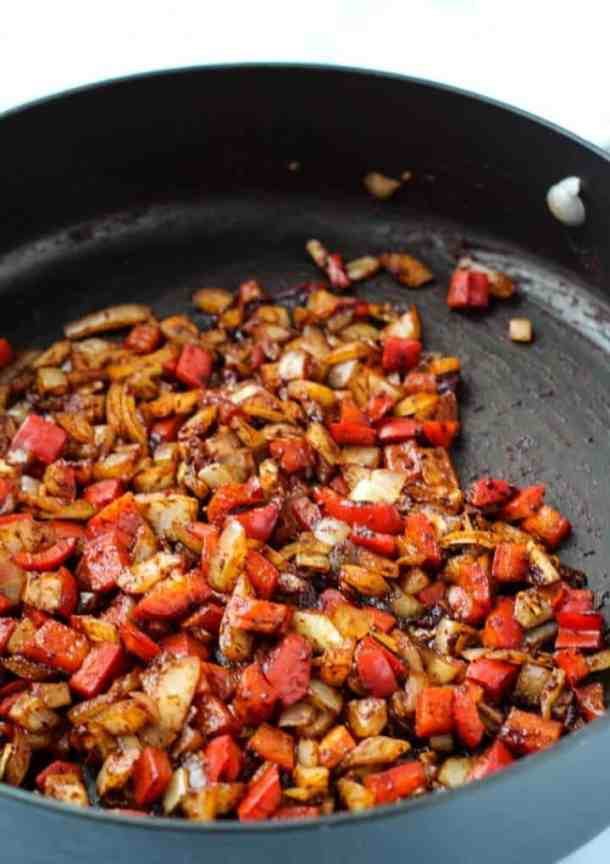 onions, peppers, and spices in pan