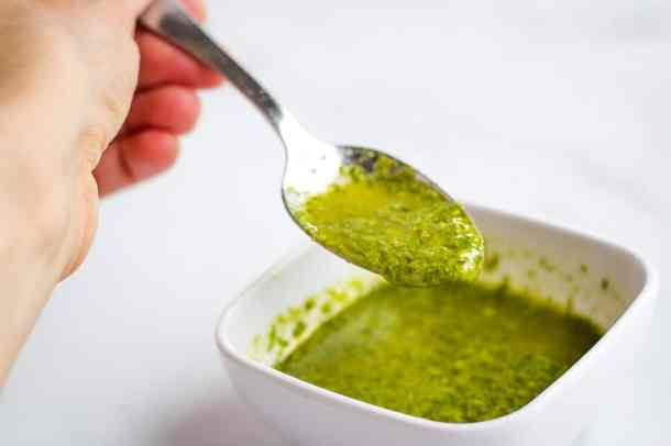 spoonful of basil sauce over small bowl