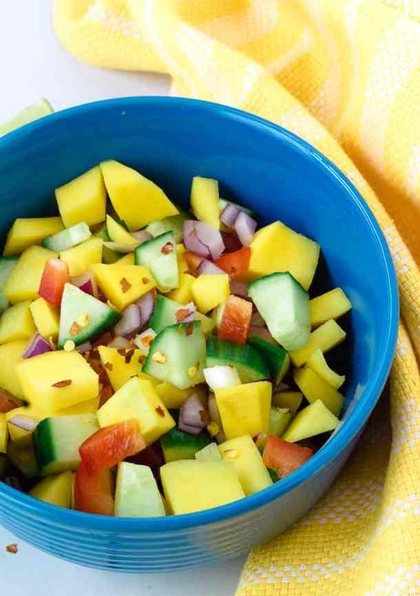 mango cucumber salad in blue bowel next to yellow towel