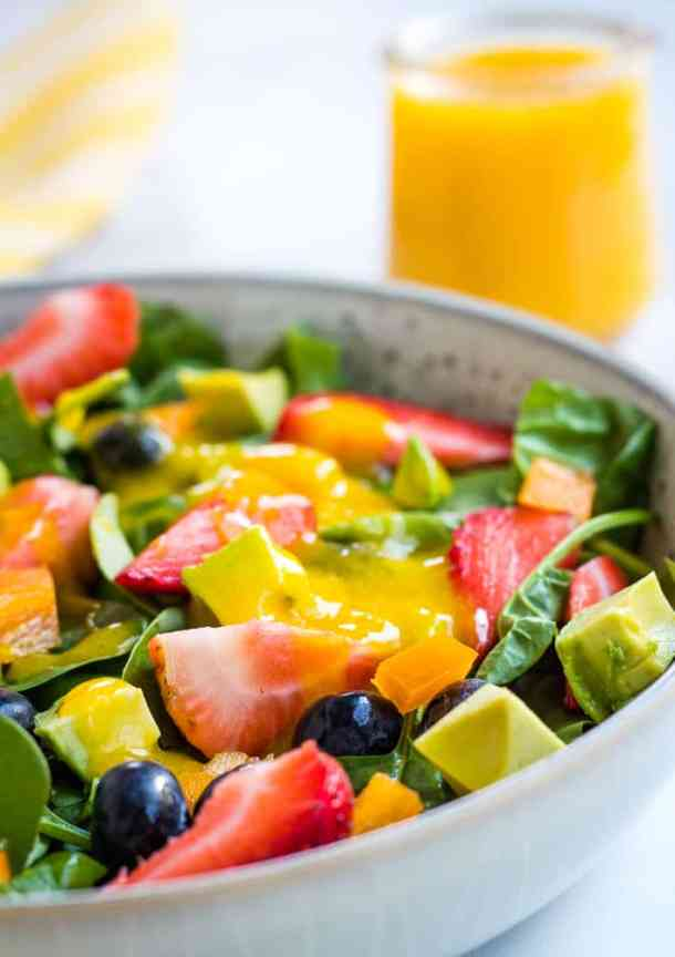 close up of berry salad with mango dressing in background