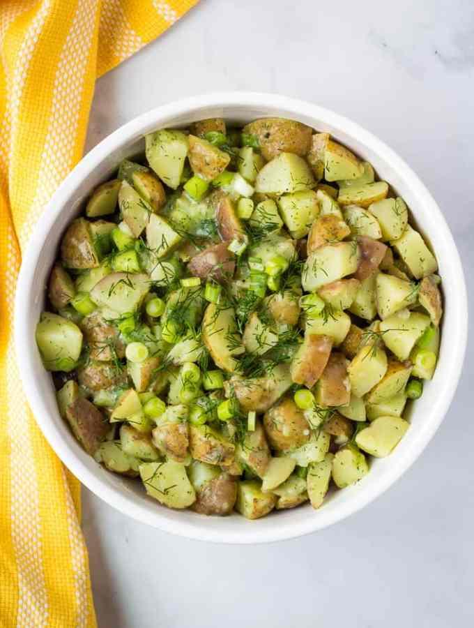 vegan potato salad with fresh herbs in white bowl