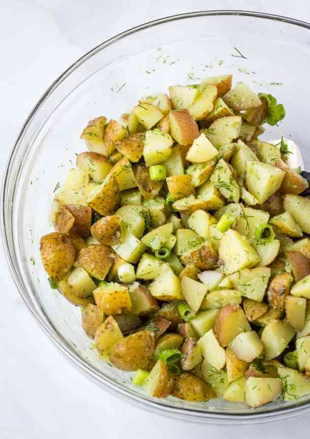 vegan potato salad with fresh herbs in glass bowl