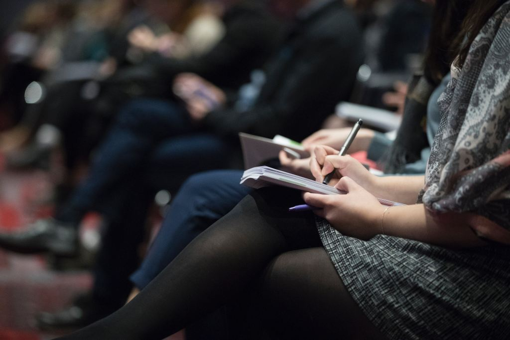 Woman Taking Notes At Conference