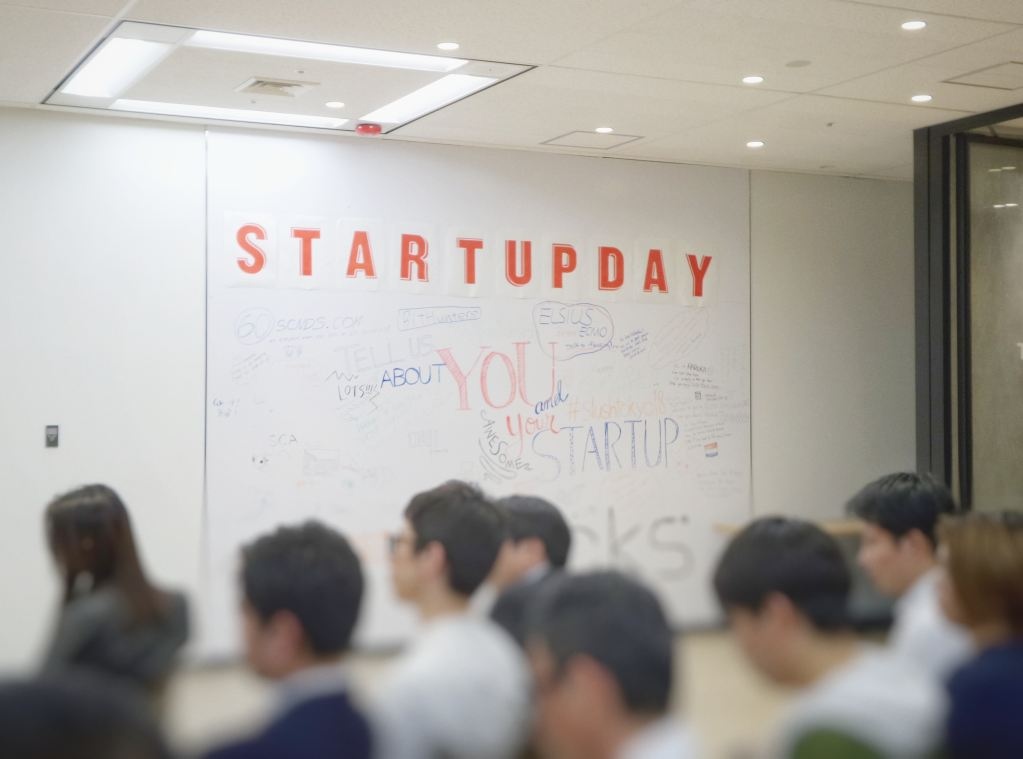 Invest in startups: Room full of people with a whiteboard that says startup day