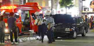 Police officials investigate an accident Saturday in which a taxi (right) veered onto a sidewalk near Kanayama Station in Nagoya, injuring seven people. | KYODO