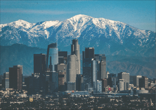 city view with snow topped mountains in background