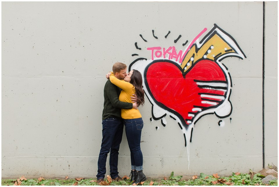 couple posing infant of graffiti wall Richmond Virginia