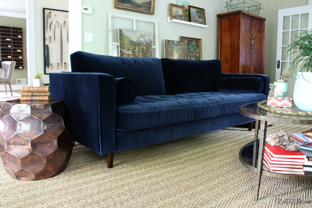 Blue is a Neutral   New Blue Sofa   Kelly Elko Mid century style blue velvet sofa   love this eclectic room with vintage  landscape gallery wall