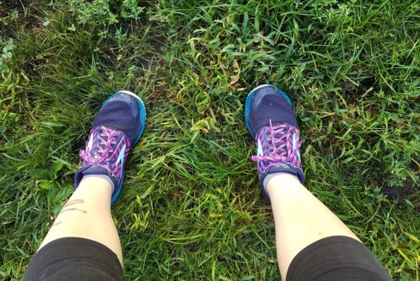 Feet in running shoes standing on the grass