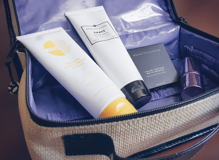 summer safe products from beautycounter -sunscreen, bronzer, shaving cream- shown in a makeup bag