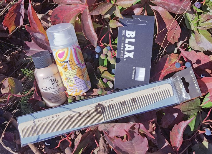 four hair products; silkomb comb, amika hair spray, blax elastics and bb pret powder on a bed of red leaves and wild blueberries