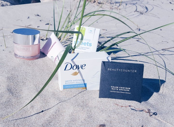 dove soap, clinique moisture surge, beautycounter bronzer, the body shop lotion and target oil wipes on a bed of beach sand