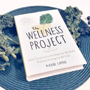 the wellness project by phoebe lapine atop some kale and a teal placemat