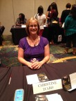 Author Christine d'Abo signing postcards for her book Quicksilver Soul.
