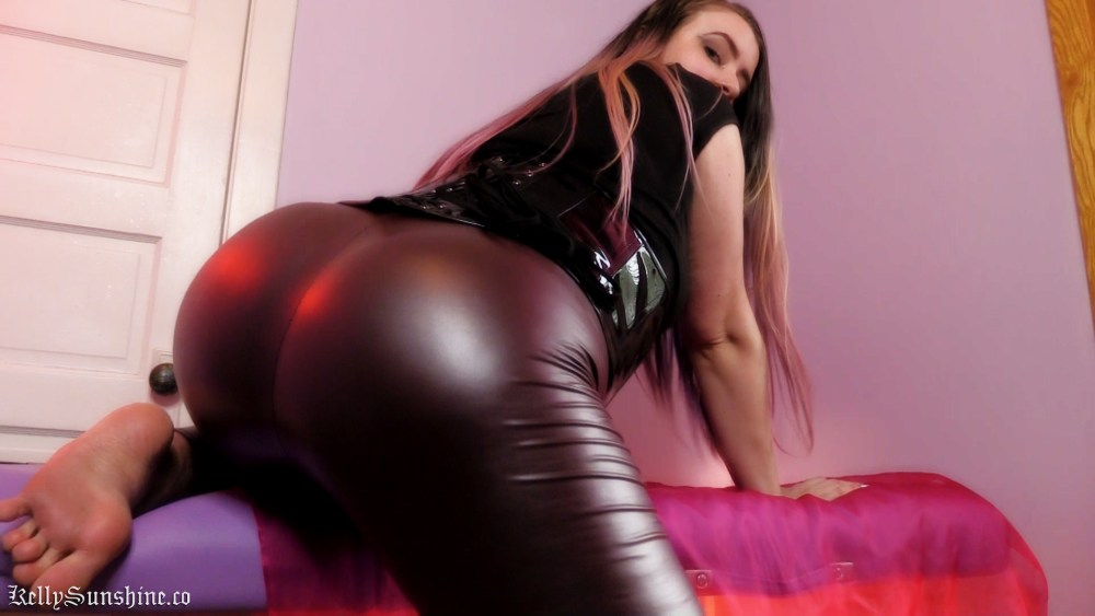 Minneapolis Mistress Femdom Clip Dominatrix Goddess Kelly Sunshine bending over showing off bare feet and curvy ass in tight leather leggings.