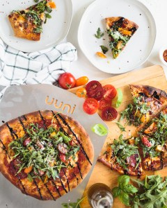 Two pizzas from above, with slices taken out of one and resting on plates nearby, with arugula and tomatoes