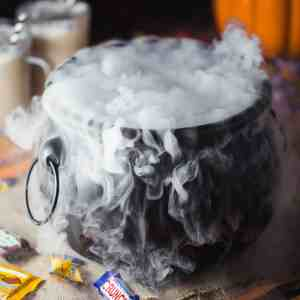 A black witch's cauldron with smoke pouring out of the top and surrounded by halloween candy and pumpkins