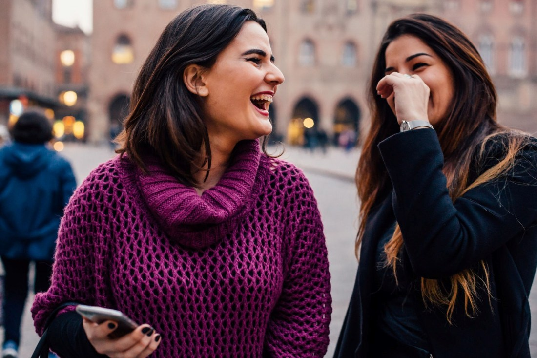 Two women delighted by an experiential marketing campaign — a key component of brand positioning strategy.