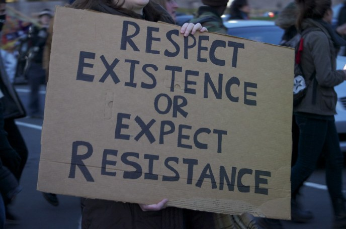 """Person at rally holding sign that reads, """"Respect existence or expect resistance"""""""