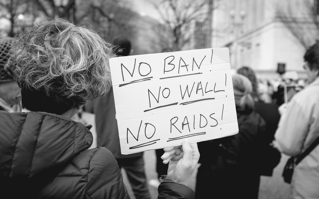 "Protester in a crowd holds a sign reading ""No Ban! No Wall! No Raids!"""