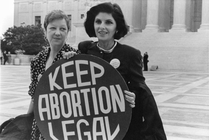 """Norma McCorvey and Gloria Allred hold a """"Keep Abortion Legal"""" sign on the steps of the US Supreme Court"""