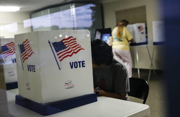 A voter sits at a voting enclosure while another stands at a voting machine in the distant background