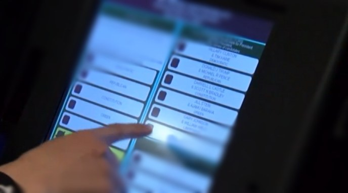 Hand selecting choices at the screen of an electronic voting machine