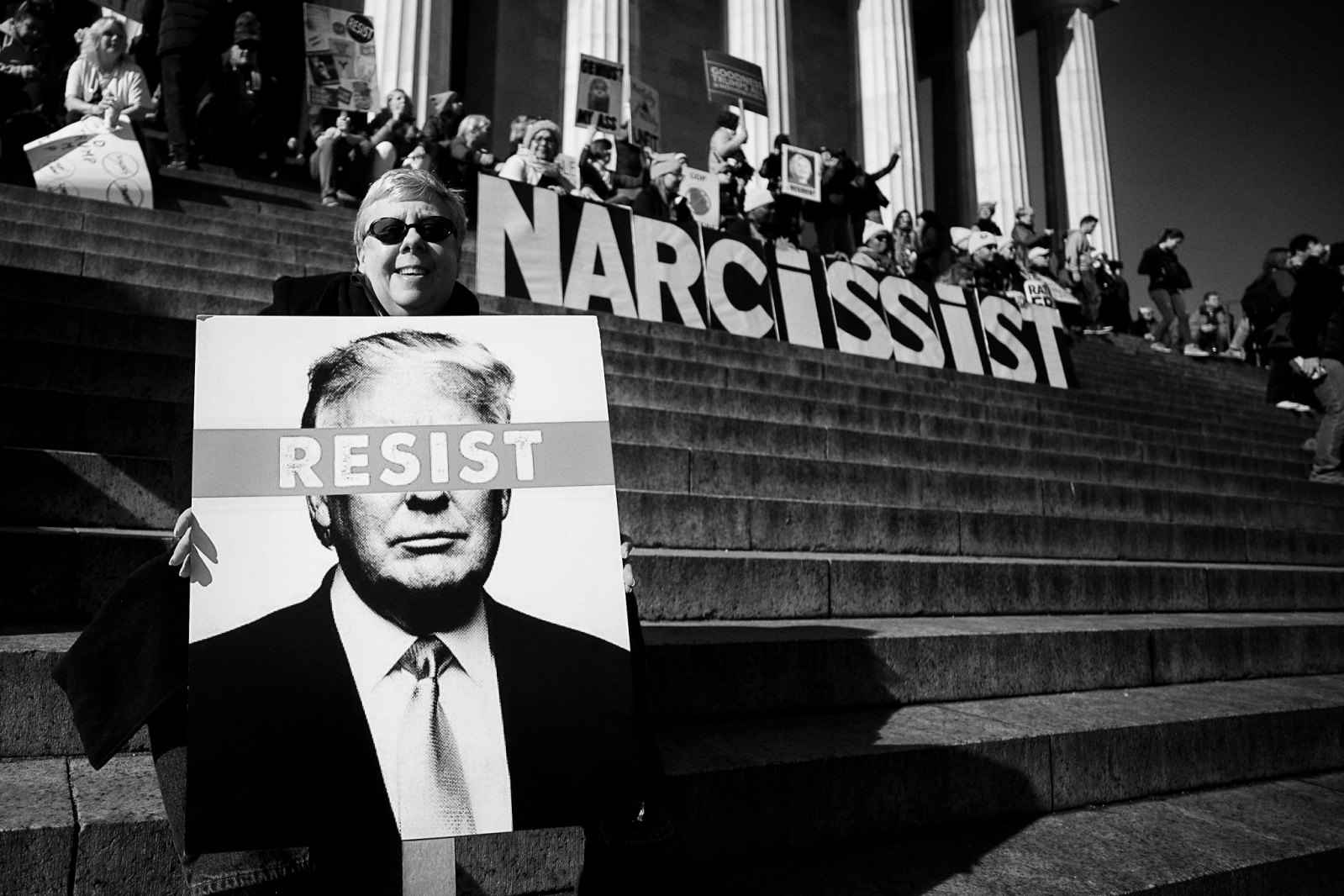 "Protest on Capital hill. Signs spell out the word ""Narcissit"" and ""Resist"""