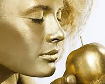 gold-painted-woman-sniffing-apple