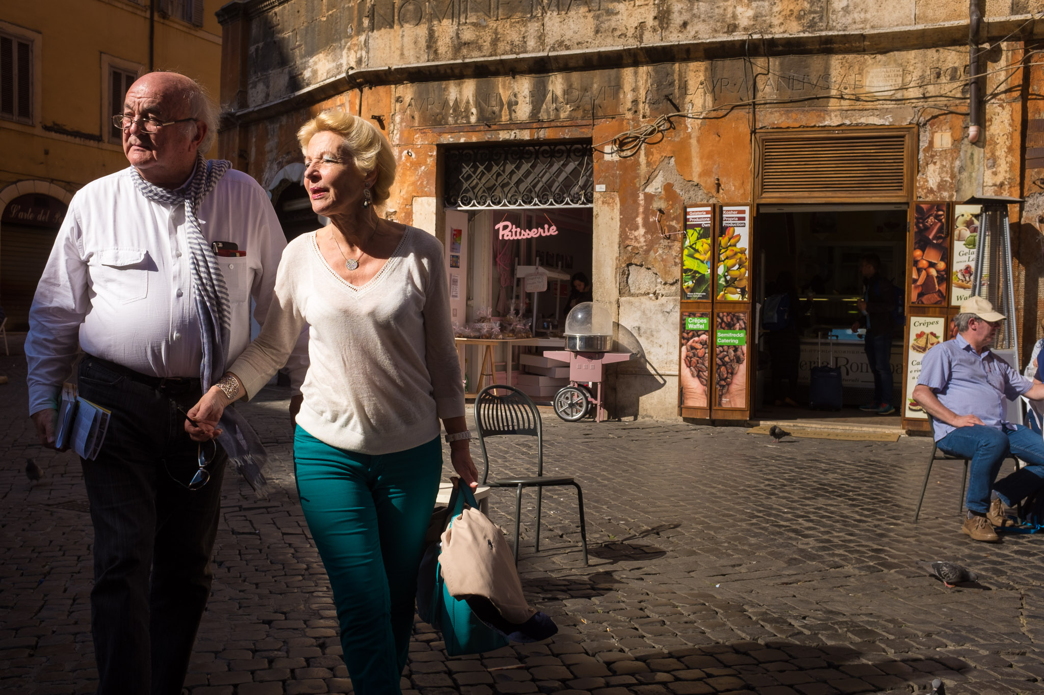 A couple walking through a shaft of light in the Jewish Ghetto in Rome