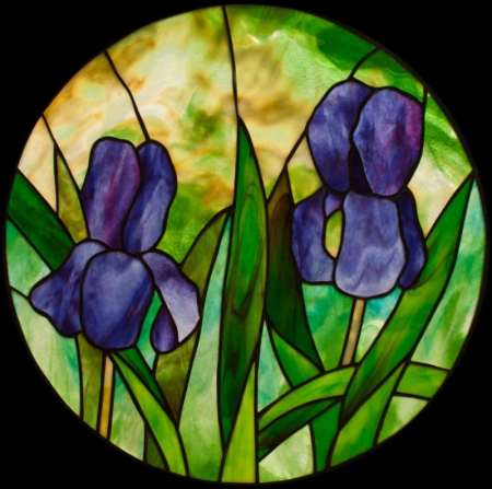 Two Irises round stained glass panel, purple irises against a amber and green background, designed by David Kennedy