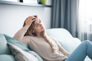 woman sitting on couch very tired