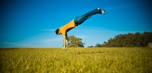 young man doing acrobatic trick in the field