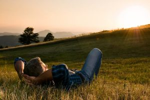 Mature man taking a break and relax in a meadow in the wonderful