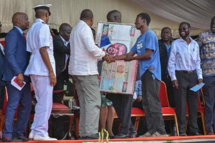 President Uhuru Kenyatta greets a Kisumu man after the man handed him a gift with his portrait in a dummy Sh500 note. December 15, 2018