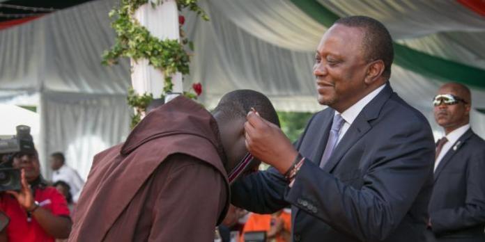 President Uhuru Kenyatta honours Peter Tabichi with the MBS award at State House on December 12, 2019